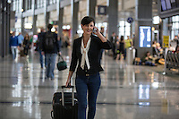 Smiling businesswoman pulls suitcase while making cell phone call in the terminal at the Austin–Bergstrom International Airport (ABIA).
