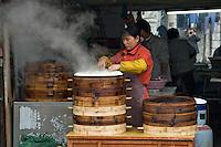 Cooking near the street in Shanghai..Shanghai, February 2006.