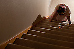 Woman lying at the bottom of stairs mystery with alcohol bottle and spilled pill bottle