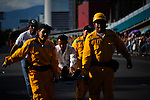 "A silletero is helped by paramedics while they attend the traditional ""Silletero"" parade during the Flower Festival in Medellin August 7, 2012. Photo by Eduardo Munoz Alvarez / VIEW."