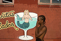An African American boy, stands in-front of a mural advertising margaritas.  Conney Island, Brooklyn. Street photography in Brooklyn NY August 4, 2007