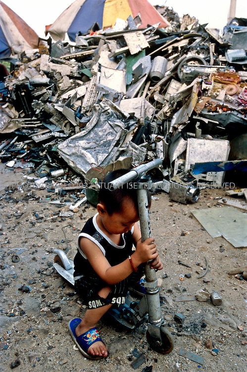 7/2/2005--Taizhou, Zheijiang Province, China..A young boy plays near piles of illegal e-waste sit outside a home in the village of Quingyu where it will be broken down and processed, releasing toxic waste into the local environment...The eastern Chinese port city of Taizhou has now become the center for much of the illegal trade in e-waste (computer waste). 24 hours a day ships arrive in the city?s harbor carrying cargo of waste, including millions of computer parts. These parts flow out of the port in trucks into the city and hinterland where hundreds of tiny work shops break down the parts, melting off the precious metals and using acids to separate gold from circuits boards, mobile phones, monitors and other computer parts. Neighborhoods are filled with the noxious and toxic fumes of this unregulated industry and thousands of men, women and children are exposed to a toxic cocktail of fumes and dust released. . .Photograph By Stuart Isett.All photographs ©2005 Stuart Isett.All rights reserved.