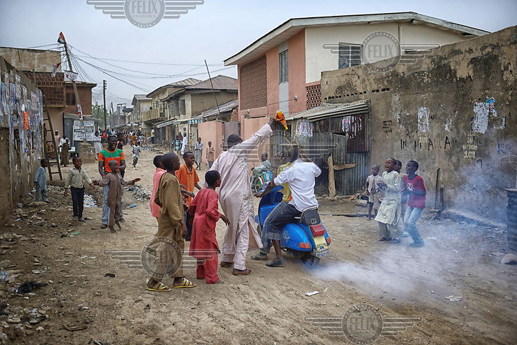 A man pours a bottle of orangeade over the head of a friend as peopel come onto the streets to celebrate the victory of Muhammadu Buhari, of the APC (All Progressives Congress Party), in the 2015 Nigerian Presidential elections.