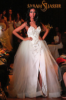 Model walks the runway in a Jewel wedding dress - modified strapless double face silk satin beaded gown with tulle over skirt, by Sarah Jassir, for the Sarah Jassir Couture Bridal Fall 2012 Opulence collection.