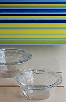 A pair of glass bowls and a striped tablecloth by Marimekko