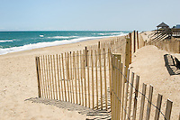 A long view of the scenic beach at Nags Head, North Carolina, where they work hard to maintain their miles of great looking beaches through constant grooming and these erosion control fences. Because of the classic ocean surf views being one of the reasons it is so attractive, the area is one of the most popular tourist destinations in the Outer Banks.