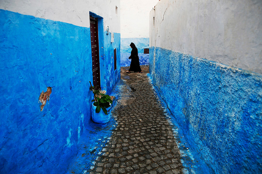 """A woman makes her way between houses painted in traditional blue and white colors in Kasbah of the Oudayas, a picturesque ancient part of Rabat September 21, 2014. Kasbah of the Oudayas, now home to about 2000 people, was built as a fortress by Almohad dynasty in 12th century at the mouth of the great Bou Regreg river. Behind walls of Medina and Kasbah of the Oudayas, ancient neighbourhoods of Morocco's capital, labyrinths of small alleys, colourful buildings and street markets offer a glimpse into city's rich history. Rabat was recently listed by UNESCO as a World Heritage Site and suggested as a """"must see"""" destination by major media outlets and tourist agencies.  REUTERS/Damir Sagolj (MOROCCO)"""