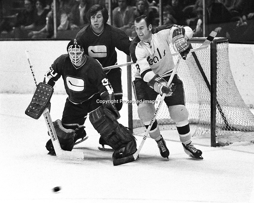Seals vs Canucks, Gerry Ehman, Canucks Barry Wilkins and goalie Dunc Wilson..1971 photo by Ron Riesterer