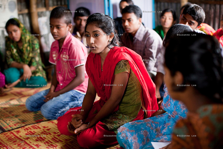 """Tamanna Jinnat (13, red scarf) speaks during a monthly meeting of a Children's Group in Bhashantek Basti (Slum) in Zon H, Dhaka, Bangladesh on 23rd September 2011. Tamanna explains, """"we have an organised system: we have a list of girls who are potential child brides and we check on them. Another initiative is making sure that there is birth registration for babies so that there will be a proof of their age."""" Tamanna's mother said that """"at your age, you are not aware of the benefits of an early marriage,"""" to which Tamanna replied, """"how about issues of maternal mortality from being too young to bear children?"""". She also wants to be allowed to work part time so she can support her own education and independence. The Bhashantek Basti Childrens Group is run by children for children with the facilitation of PLAN Bangladesh and other partner NGOs. Slum children from ages 8 to 17 run the group within their own communities to protect vulnerable children from child related issues such as child marriage. Photo by Suzanne Lee for The Guardian"""