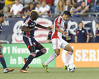 Toronto FC midfielder Matias Laba (20) works to clear ball as New England Revolution midfielder Saer Sene (39) defends. In a Major League Soccer (MLS) match, Toronto FC (white/red) defeated the New England Revolution (blue), 1-0, at Gillette Stadium on August 4, 2013.