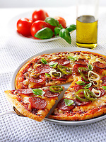 Pizza topped with Pepperoni, cheese, chilli & basil with a slice out photo.Funky Stock pizzas photos