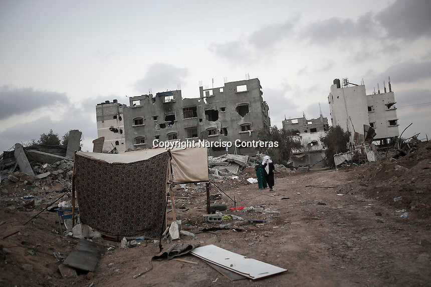 """In this Sunday, Aug. 17, 2014 photo, Palestinian women walk through what remains from her house as they look for their belongings after it was destroyed during the """"Protective Edge"""" Israeli military operation in Shuyaja neighborhood in Gaza City. After a five days truce was declared on 13th August between Hamas and Israel, civilian population went back home looking for their goods in Gaza Strip. (Photo/Narciso Contreras)"""
