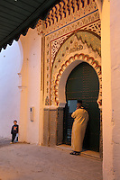Entrance to a mosque consisting of green studwork doors within a horseshoe arch decorated with zellige tiles and painted stucco on a street in the medina or old town of Tetouan, on the slopes of Jbel Dersa in the Rif Mountains of Northern Morocco. Tetouan was of particular importance in the Islamic period from the 8th century, when it served as the main point of contact between Morocco and Andalusia. After the Reconquest, the town was rebuilt by Andalusian refugees who had been expelled by the Spanish. The medina of Tetouan dates to the 16th century and was declared a UNESCO World Heritage Site in 1997. Picture by Manuel Cohen