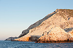 Sea of Cortez, Baja California, Mexico; a small rock island, Morro One, covered in bird droppings, illuminated with warm early morning sunlight, sits adjacent to San Pedro Martir Island