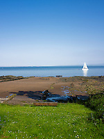 A sailing boat on the calm waters seen from the shoreline at the end of the property