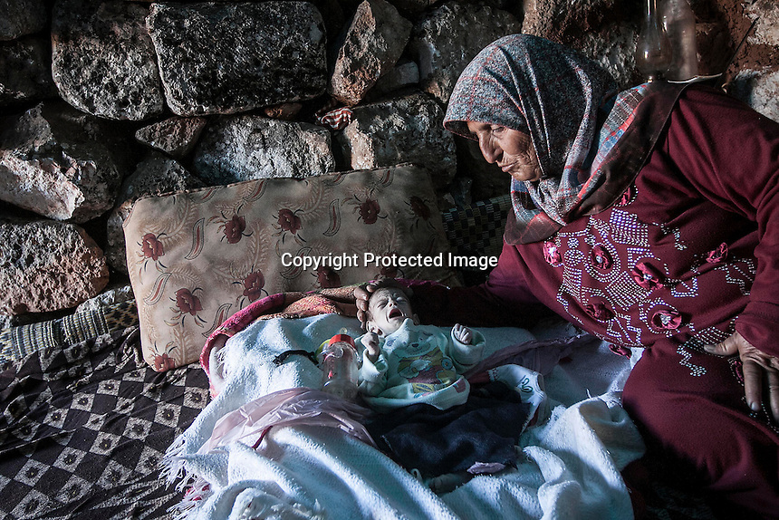 """In this Friday, Sep. 27, 2013 photo, a Syrian displaced woman conforts her one-month old grandson inside a stone house at the Kafr Ruma, an ancient roman ruins used as temporary shelter by those families who have fled from the heavy fighting and shelling in the Idlib province countryside of Syria. Dozens of families settled in the ancient ruins known as """"The Forgotten City"""" and declared human heritage by UNESCO, when the clashes between opposition fighters and government forces broke out in the region since more than two years ago. (AP Photo)"""