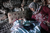 "In this Friday, Sep. 27, 2013 photo, a Syrian displaced woman conforts her one-month old grandson inside a stone house at the Kafr Ruma, an ancient roman ruins used as temporary shelter by those families who have fled from the heavy fighting and shelling in the Idlib province countryside of Syria. Dozens of families settled in the ancient ruins known as ""The Forgotten City"" and declared human heritage by UNESCO, when the clashes between opposition fighters and government forces broke out in the region since more than two years ago. (AP Photo)"