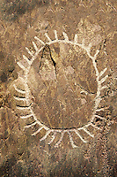 "Prehistoric  petroglyphs, rock carvings, of a sun design carved by the the prehistoric Camuni people in the Copper Age around the 3rd milleneum BC, Stele ""Bagnolo 1"" found in 1963 from Malegno near Bangnolo Ceresolo. Museo Nazionale della Preistoria della Valle Camonica ( National Museum of Prehistory in Valle Cominca ), Lombardy, Italy. Grey Art Background"