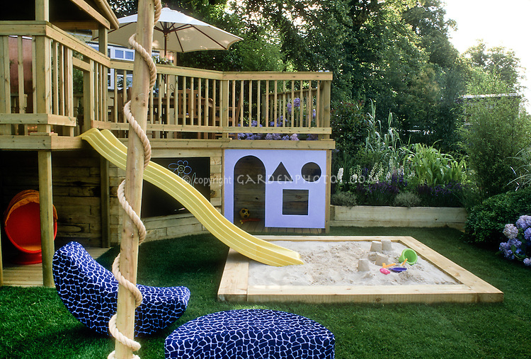 Deck with kids in mind. Design: Boardman, Gelly & Co. Sandbox, sliding board pond, home landscaping, colorful backyard playground, lawn grass, chalk board, entertaining children at home