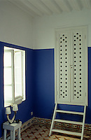 A simple white cupboard is accessed by a small set of steps in this blue and white painted bedroom