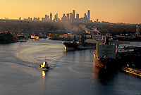 Tugboat at Port of Houston and downtown Houston skyline at sunset