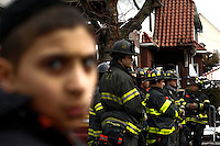 NYFD officers stay in front of the house where at least 7 children died during the fire in Brooklyn, New York. 21.03.2015. Eduardo Munoz Alvarez/VIEWpress.