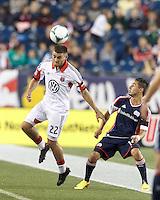 D.C. United defender Chris Korb (22) heads the ball. New England Revolution midfielder Diego Fagundez (14). In a Major League Soccer (MLS) match, the New England Revolution (blue) defeated D.C. United (white), 2-1, at Gillette Stadium on September 21, 2013.