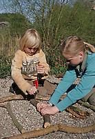 Kinder basteln Klangspiel aus Ästen, Junge bohrt mit Handbohrer ein Loch in Ast