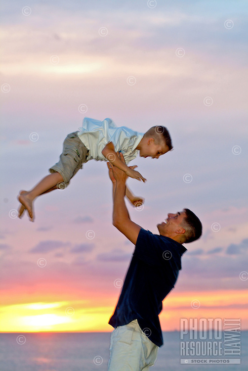 Father throwing son up in the air near the ocean at magic island park, Oahu