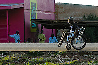 ldobson@wbhq.com 512 627-1841- Uganda- A Free Wheelchair Mission recipient stoically makes his way home after recieiving a wheelchair along with 60 others.