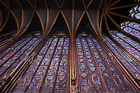 View from below of the stained glass clerestories of the nave and choir (right), upper chapel of La Sainte-Chapelle (The Holy Chapel), 1248, Paris, France. La Sainte-Chapelle was commissioned by King Louis IX of France to house his collection of Passion Relics, including the Crown of Thorns. Fifteen huge mid-13th century windows fill the nave and apse of La Sainte-Chapelle. Each window group has four lancets topped by three rose windows. In the choir, the windows have only two lancets. Picture by Manuel Cohen