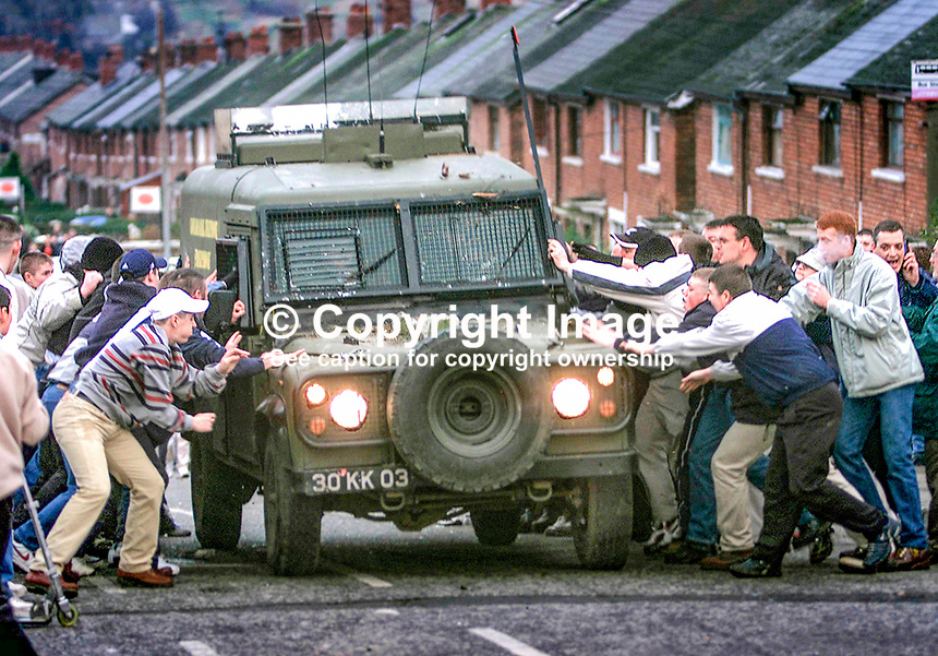 Republican rioters in Alliance Avenue, Ardoyne, Belfast, N Ireland, UK, attempt to overturn a British Army Landrover. January 2002. 200201024. <br />