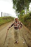 A coffee farmer with white hat and walking stick on the country road outside Salento, Colombia