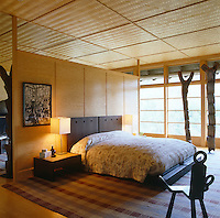 A Japanese-style bedroom with the contemporary bed placed against a free-standing panel of pale wood and the windows designed to resemble Japanese screens