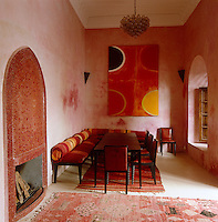 A painting by Terry Frost hangs on the far wall of this dining room which has a fireplace decorated with red mosaic tiles