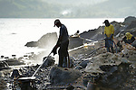 Workers spray rocks along the shoreline in Botongon, a neighborhood of Estancia, Philippines, in an effort to remove oil that spilled there when Typhoon Haiyan swept through the area in November 2013. The storm was known locally as Yolanda. Most residents who lived along the affected coastline remain camped in temporary shelters elsewhere, despite government efforts to get many to return. The ACT Alliance is accompanying them as they struggle to survive.