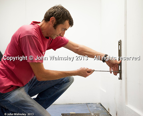 Trainee plumber, here fitting the brackets fort a rediator, Able Skills training centre, Dartford, Kent.