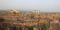 General view of Volubilis on a fertile plain in Northern Morocco, with the Triumphal Arch of Caracalla, 217 AD, on the left and the Portico leading to shops on the main street or Decumanus Maximus on the right. Volubilis was founded in the 3rd century BC by the Phoenicians and was a Roman settlement from the 1st century AD. Volubilis was a thriving Roman olive growing town until 280 AD and was settled until the 11th century. The buildings were largely destroyed by an earthquake in the 18th century and have since been excavated and partly restored. Volubilis was listed as a UNESCO World Heritage Site in 1997. Picture by Manuel Cohen