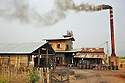 Sugar refinery in a rural area of North East Burma. A rudimental building with a smoky chimney where the sugar syrup is converted into sweet crystals.