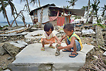 Nicole Adona, 5, and her brother Gilbert, 6, play in the rubble of what was once their family's home on Jinamoc Island, part of the municipality of Basey in the Philippines province of Samar that was hit hard by Typhoon Haiyan in November 2013. The storm was known locally as Yolanda. The ACT Alliance has been providing a variety of assistance to survivors here, and is planning a long-term rehabilitation program with residents.
