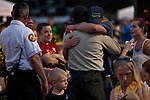 Firefighters and family members of the Granite Mountain Hotshots, 19 of who perished in the Yarnell Fire Sunday, embrace at a vigil at Prescott High School in Prescott, Arizona, July 2, 2013.