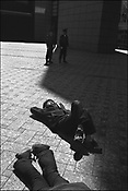 Watched by police, two anti-Iraq war demonstrators lie in the sunshine, near the American embassy in Tokyo. Japan, 2003.