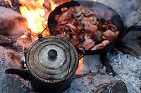 Bacon cooks over a campfire while a kettle keeps warm in the ashes.