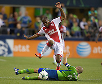 Darlington Nagbe, left, of the Portland Timbers hurdles Osvaldo Alonso of the Seattle Sounders FC during play at CenturyLink Field in Seattle Saturday August, 3, 2013. The Sounder won the match 1-0.