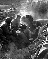 These men of the Heavy Mortar Co., 7th Inf. Regt., go native, cooking rice in their foxhole in the Kagae-dong area, Korea.  December 7, 1950.  Pfc. Donald Dunbar.  (Army)<br /> NARA FILE #  111-SC-354103<br /> WAR &amp; CONFLICT BOOK #:  1472
