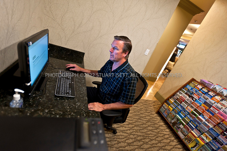 """9/27/2011--Seattle, WA, USA..Don Corbin, 50, from Danville, CA, using the business center, just off the main lobby, at the Silver Cloud Hotel in Seattle, WASH. Corbin was visiting Seattle on vacation so did not have a laptop with him and needed to use the business center to print out boarding passes...Business travelers armed with laptops, smartphones and wifi cards, are eschewing hotel business centers in favor of working in their rooms or the lobby, and hotels across the price spectrum have added the trappings of those business centers to where the guests are. Hotel business centers are still used by travelers who have a document or boarding pass to print, or need to check email and don't have their laptop, but they will usually get in and out quickly, rather than spend hours working there. And the business centers themselves are likely to be small rooms with just a few computers and printers. The Silver Cloud Hotel in Seattle, part of a ten-hotel chain in the Northwest, offers up two workstations and two printers, """"and business people barely use them,"""" said the hotel's general manager Chauncey DeVitis. The free WiFi and the copy machine behind the front desk seems to meet the needs of most business travelers these days, he said...©2011 Stuart Isett. All rights reserved."""
