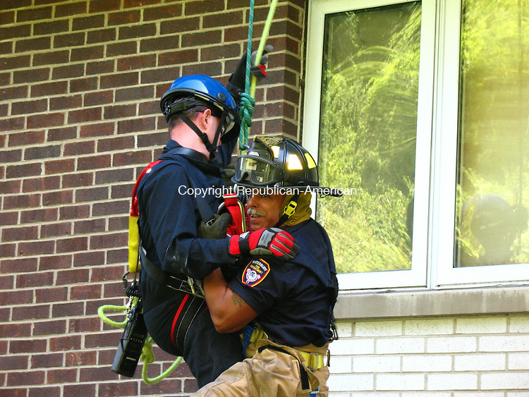 WATERBURY, CT - 19 September 2008 - Waterbury firefighters conducted rope rescue drills Thursday morning at the seven-story Begg Apartment building on Bank Street in the Brooklyn neighborhood. Alfredo Santiago, right, a 25-year veteran, was rescued from a sixth-story window by Mark Moran, left, who rappelled down from the rooftop. The drill was conducted by fire Lt. Tony Leca of Rescue Engine 9.