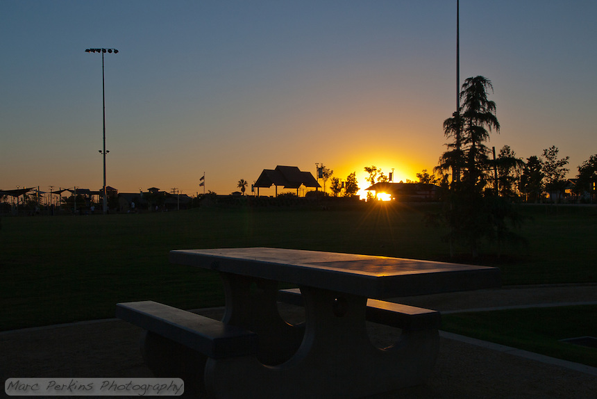 The setting sun goes behind the picnic pavilion at Stanton Central Park, reflecting light off of a picnic table with a built in chessboard.