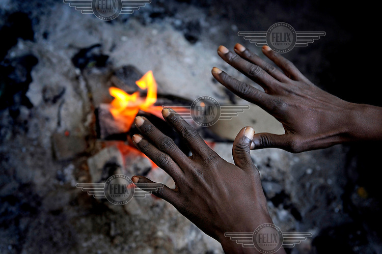 A group of illegal migrants warm themselves by a fire in the grounds of an industrial estate where they sleep outside while they wait for work picking olives. The picking season starts in November when thousands of seasonal workers arrive to work in the groves. This is work usually carried out by migrant workers from overseas but the collapse in Spain's economy and rocketing levels of unemployment has led to many Spaniards seeking to work as pickers, labour they had previously shunned.