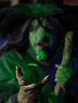 Scary old witch with outstretched hand illuminated with eerie green lighting. Selective focus photo.